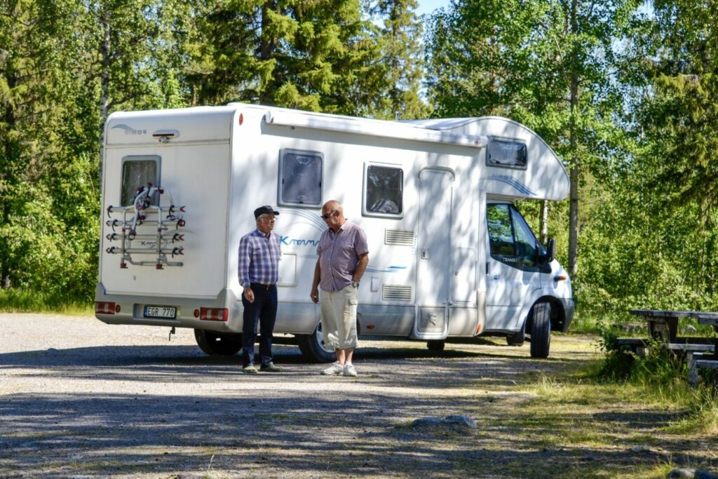 Two men standing outside an rv discussing their boondockers welcome regrets.