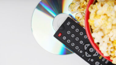 A DVD player remote, a bowl of popcorn, and a shiny DVD.